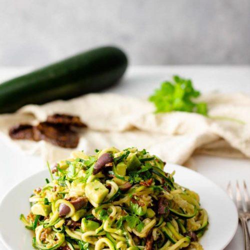Fettfasten Rezepte bestehen nicht nur aus purem Fett. Es darf durchaus auch ein wenig Gemüse dabei sein. Wobei die Zucchini mit Avocado und Oliven auch super als Low Carb oder keto Beilage zu einem Hähnchen passt. Oder noch besser, zu Scampi. #fettfasten #zudeln #zucchininudeln #zoodels #fettfastenrezepte #abnehmenrezepte #gemüsenudeln